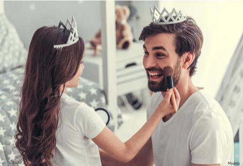 Daughter putting makeup on her dad