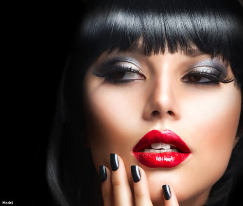 Woman with jet black hair and red lipstick