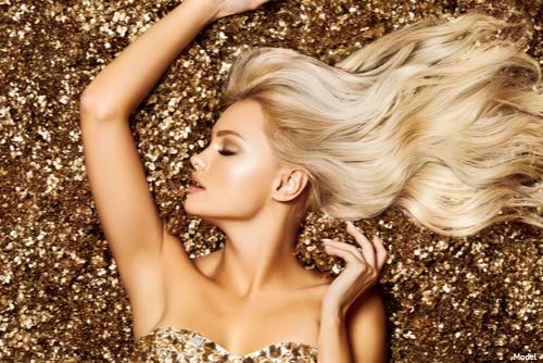 Woman laying on a bed of gold glitter